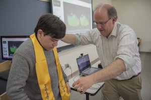 Honors Program Director Prof. Thomas Maulucci presents senior Cole Ludorf with his honors sash.