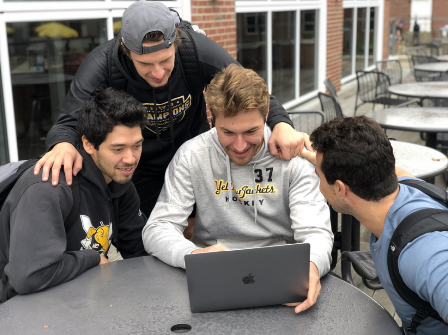 Members of the AIC Hockey Team chatting while enjoying the music outside the Hive