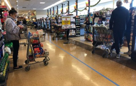 Customers stand behind floor markers to remain at least six feet apart in line