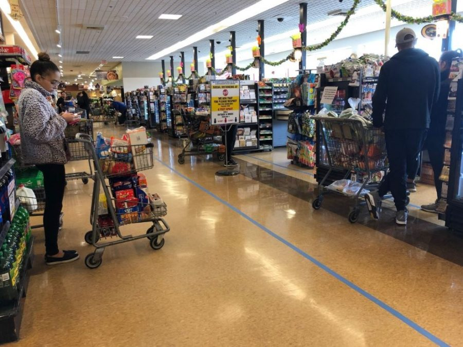 Customers+stand+behind+floor+markers+to+remain+at+least+six+feet+apart+in+line